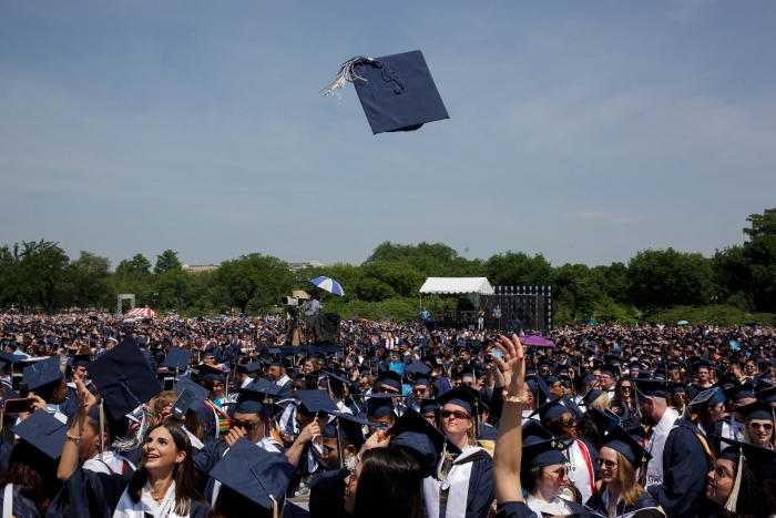 crowd of graduates with one cap thrown in air