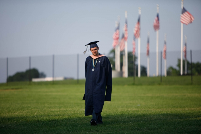 graduate walking on National Mall with American flags behind him