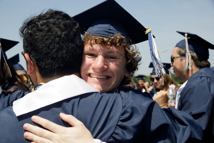students embracing in commencement attire