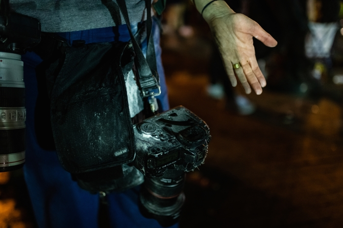 Image of a person with a camera covered in debris