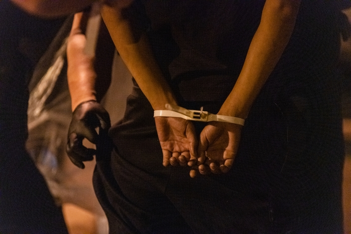 Image of a person's hands bound by zipties