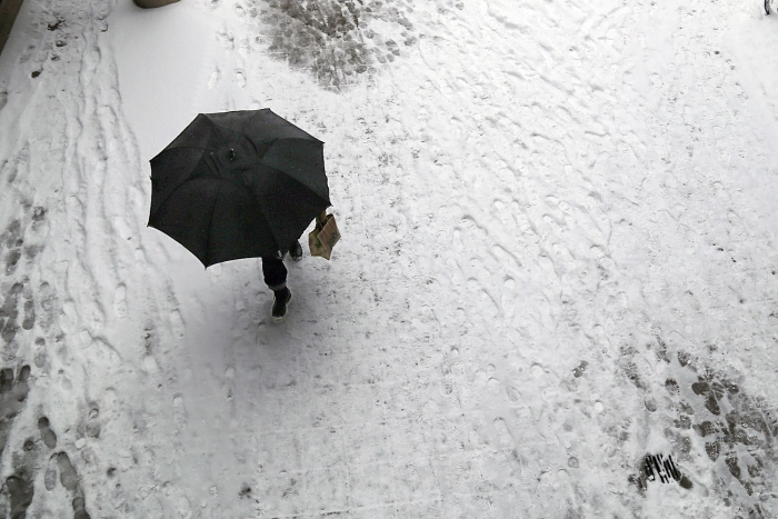 A lone pedestrian, with an umbrella for cover, walks through the snow-covered breezeway of the Academic Center. (Rob Stewart/GW