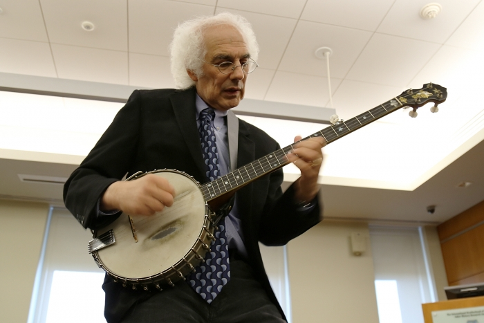 Stephen Wade performs a traditional song on banjo during the symposium.