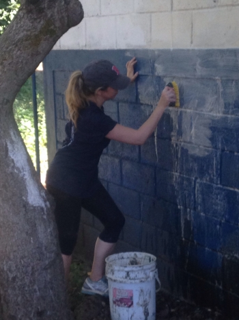 A student cleans a wall of the El Manzano Uno elementary school before painting it.