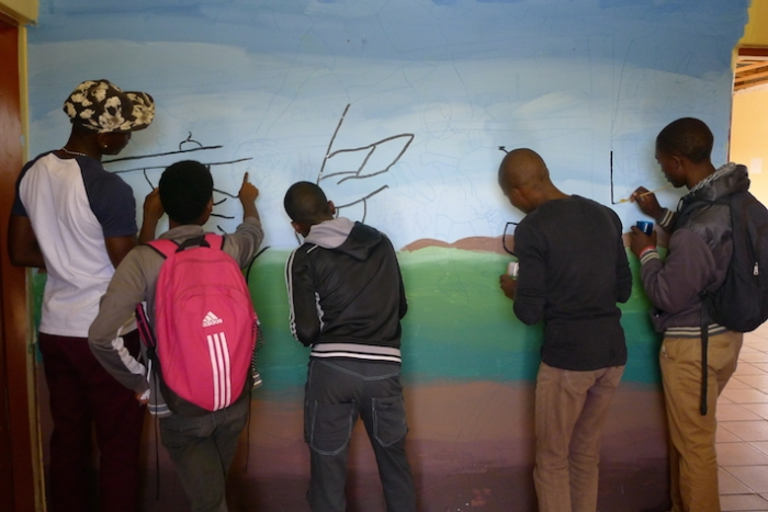 Students and young South Africans paint murals for the Bokamoso Youth Center.