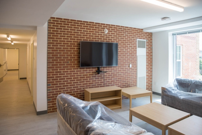 flatscreen tv against exposed brick wall with sofa and chairs