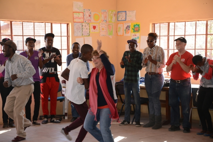 Professor Leslie Jacobson dances with young South Africans in the Bokamoso Youth Center.