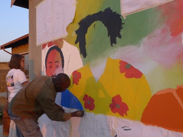 Students and young South Africans paint a mural for the Bokamoso Youth Center.