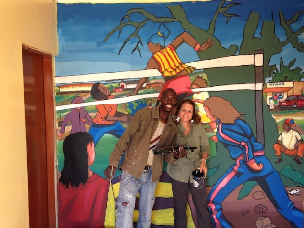 Professor Tally Tripp helps paint a mural at the Bokamoso Youth Center.