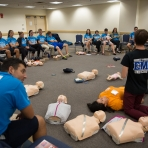 Volunteers learn CPR. (Photo: Zach Marin)