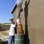 Bokamoso staff apply plaster to a wall to get it ready for mural painting.