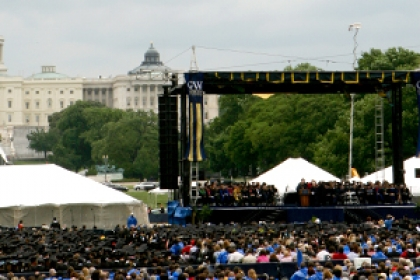 graduates on National Mall during commencement with Capitol as backdrop to university stage