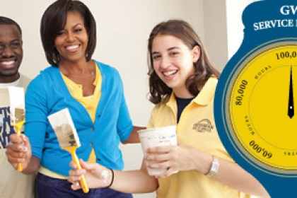 Michelle Obama with students with paint brushes and graphical representation of clock pointing to 100,000-hour service challenge