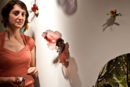 Ana Labastida stands by glass moths on display in exhibition