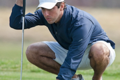 Andres Pumariega crouches down with golf club to assess next stroke