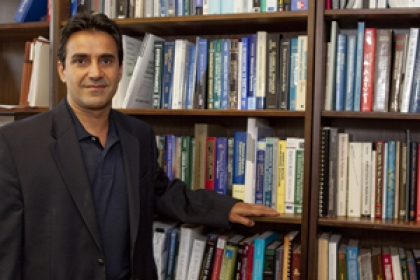 Azim  Eskandarian stands in front of books on stacks