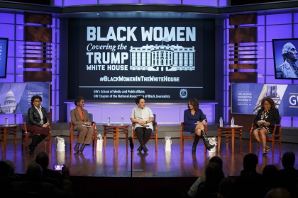 """Black Women Covering the White House"" on screen with panelists seated on stage in front of screen"