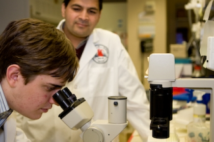 Caleb Seavey at microscope with another researcher looking on