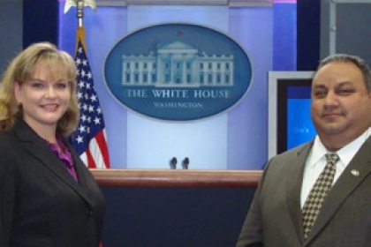 Jackie and Gilbert Cisneros smiling at White House in front of press room podium
