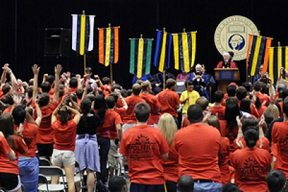 view of freshman convocation including freshmen in matching shirts and Steven Knapp in regalia at podium on stage