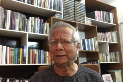 Muhammad Yunus gives virtual talk in front of a book shelf