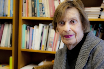 Faye Moskowitz sits with stacks of books behind her