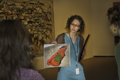 Faye Gleisser holds up a printed piece of art to a group of people in the National Gallery of Art