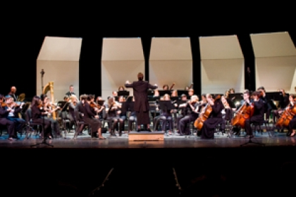 GW orchestra on stage with conductor raising batons