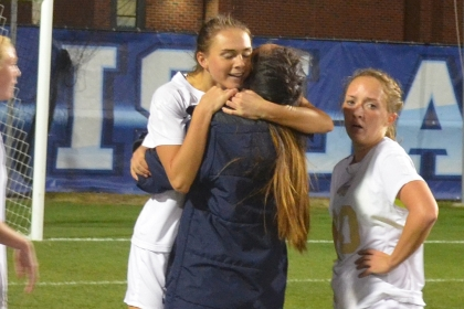 GW  junior MacKenzie Cowley embraces teammates after the Colonials win. (Photo/GW Athletics)