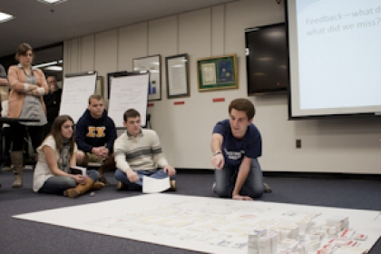 group of people on floor reviewing plans for Gelman Library renovations