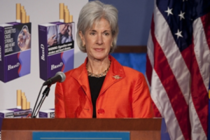 HHS Secretary Kathleen Sebelius speaks at podium with flags behind her