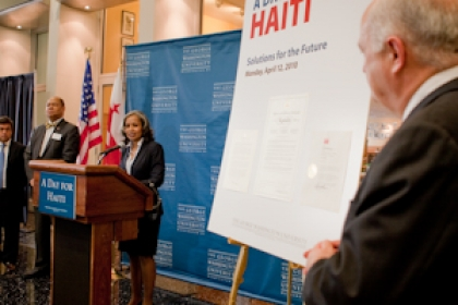 Steven Knapp viewing female speaker at podium at a Day for Haiti event