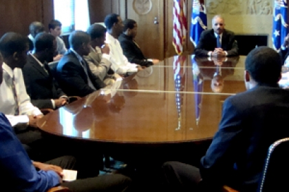 Eric Holder at head of table in DOJ with members of the basketball team sitting around the table listening
