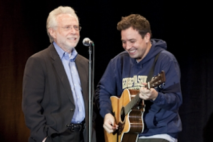 Jimmy Fallon with guitar wearing a George Washington University sweatshirt alongside Wolf Blitzer