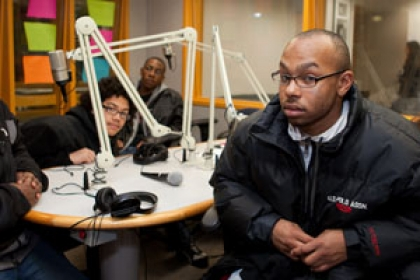 students seated at table in WRGW studio surrounded by microphones