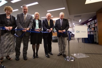 geLman ribbon cutting, administrators lined up with scissors to cut ribbon ceremoniously