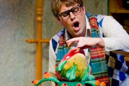 Student performing in Little Shop of Horrors with blood-thirsty plant
