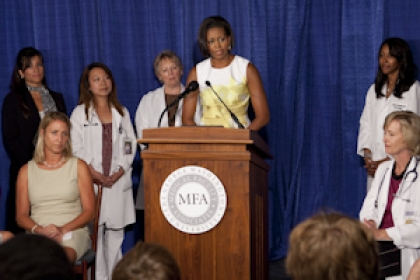 Michelle Obama at podium with Jill Biden, Kathleen Sebelius and others standing behind her