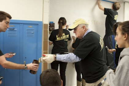 students work with Steven Knapp in high school hallway painting