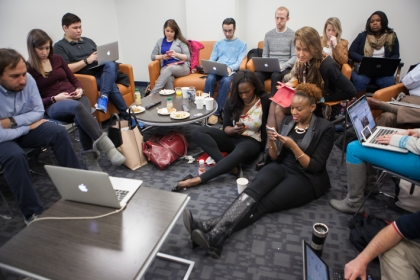 Group of students in lounge around laptops and mobile views live tweeting Meet the Press