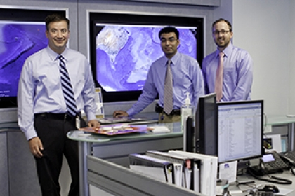 members of GW's Maritime Medical Access stand in front of screens with aerial views of world on them