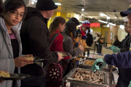 Steven Knapp in baseball hat serving sausage to a group of students at Midnight Breakfast