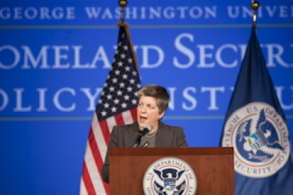 Janet Napolitano delivers speech at a DHS podium with American and Department of Homeland Security flags behind her