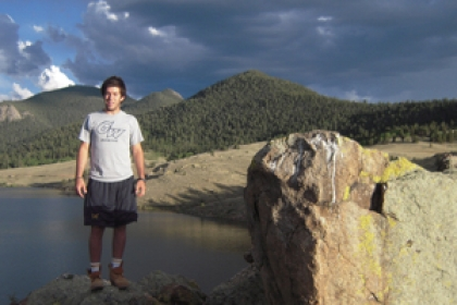 male wearing George Washington University shirt stands in mountains overlooking body of water