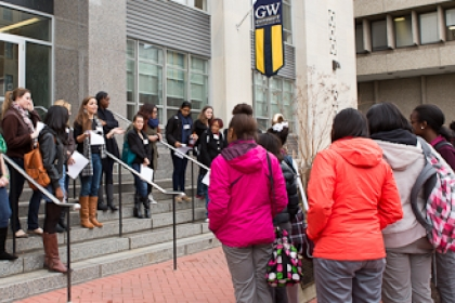 Students gathering in group on stairs outside of GW academic building
