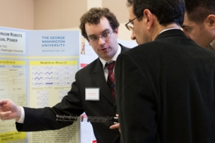 student points to presentation board at showcase with two people reviewing his work