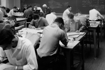 historical view of students sitting at tables working paper and pencils