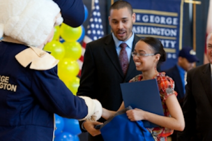 student shaking mascot George's hand when she is awarded SJT scholarship with her family and President Knapp looking omn