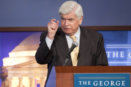 Chris Dodd speaks at podium with plaque The George Washington University. Backdrop also reads The George Washington University