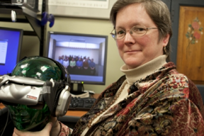 Shelly Brundage smiles in office at desk holding virtual reality headset